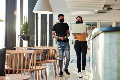 Buy stock photo Shot of a masked young businessman and businesswoman using a laptop while walking through a modern office