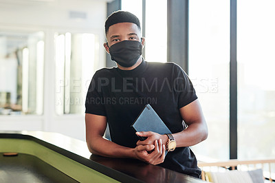 Buy stock photo Portrait of a confident masked young businessman standing at the front desk of a modern office