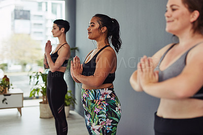Buy stock photo Shot of a group of young women meditating during a yoga class