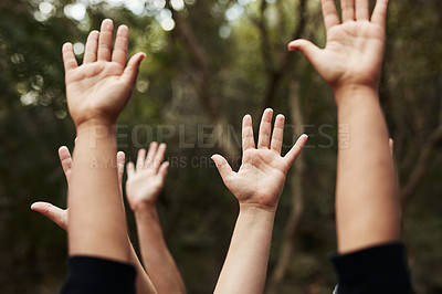 Buy stock photo Cropped shot of a group of unrecognisable people raising their hands out in nature