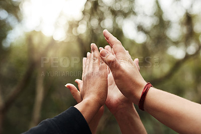 Buy stock photo Cropped shot of a group of unrecognisable people joining hands out in nature