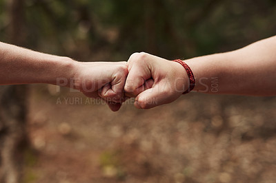 Buy stock photo Cropped shot of two unrecognisable men bumping fists out in nature