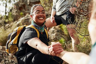 Buy stock photo Shot of two young women reaching for each other's hands on a hiking trail