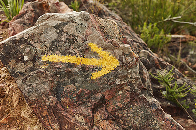 Buy stock photo Shot of a yellow arrow painted on a rock on a hiking trail