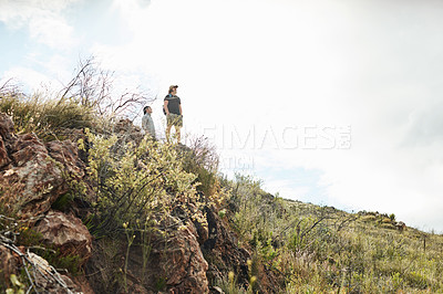 Buy stock photo Shot of two young men admiring the view while out hiking in nature