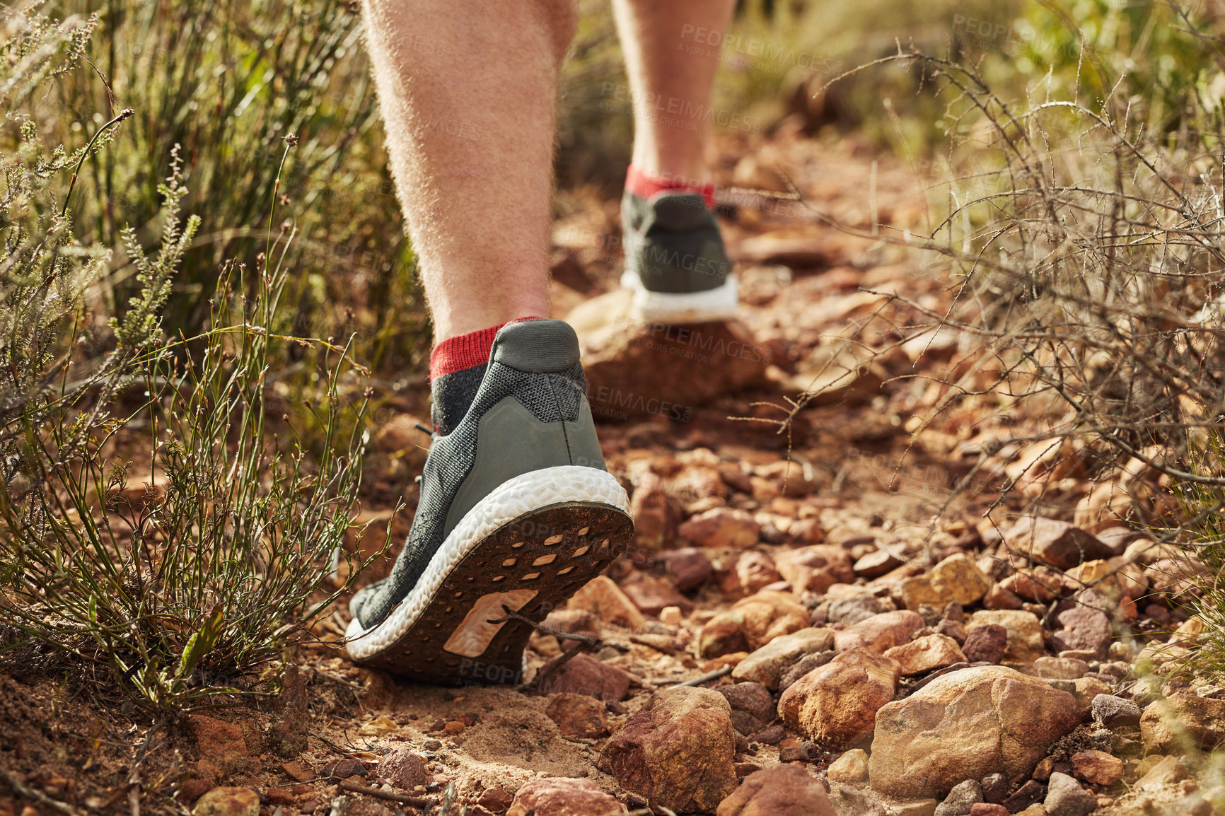 Buy stock photo Cropped shot of an unrecognisable man walking along on a rocky hiking trail