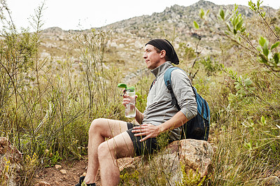 Buy stock photo Shot of a young man taking a break and drinking water while hiking in nature