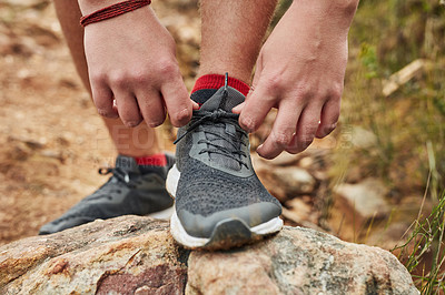 Buy stock photo Cropped shot of an unrecognisable man tying his shoelaces while hiking along on a rocky hiking trail