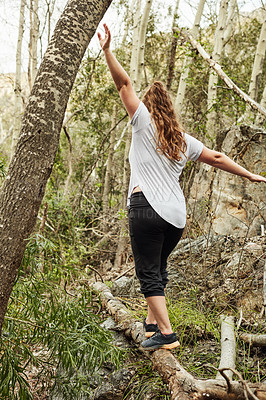 Buy stock photo Shot of an unrecognisable  young woman walking on a log along a hiking trail