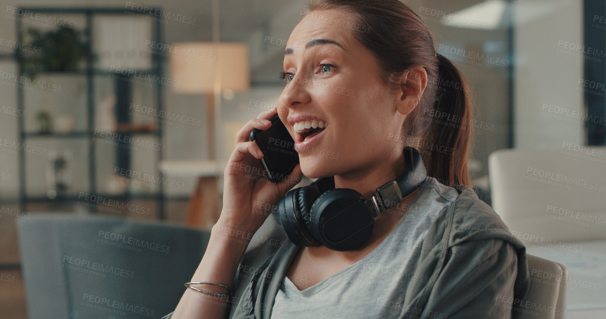 Buy stock photo Shot of a young designer looking surprised while talking on a cellphone in an office