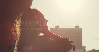 Buy stock photo Shot of a young woman listening to music through headphones while standing outside