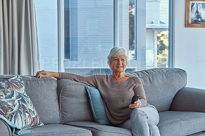 Buy stock photo Shot of a senior woman relaxing on the sofa and watching tv