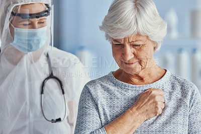 Buy stock photo Shot of a senior woman feeling pain in her chest during a consultation with a doctor