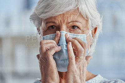 Buy stock photo Shot of a senior woman wearing a face mask in a hospital