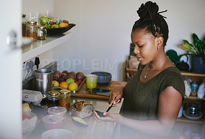 Buy stock photo Cropped shot of a young woman making herself a sandwich at home