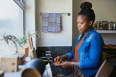 Buy stock photo Cropped shot of a young woman washing the dishes at home