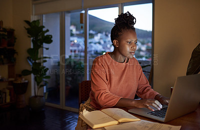 Buy stock photo Shot of a young woman using a laptop at home at night