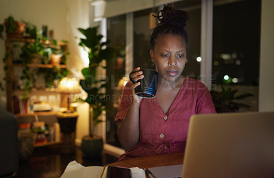 Buy stock photo Shot of a young woman drinking coffee while using a laptop at home at night