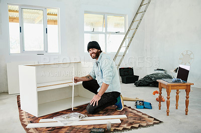 Buy stock photo Shot of a young man assembling a wooden shelf at home