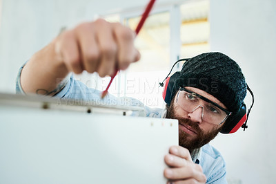 Buy stock photo Shot of a young man making measurements while assembling wooden furniture at home