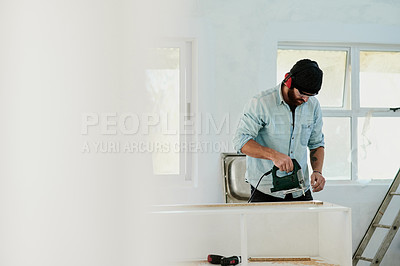 Buy stock photo Shot of a young man using a power tool to cut a piece of wood at home