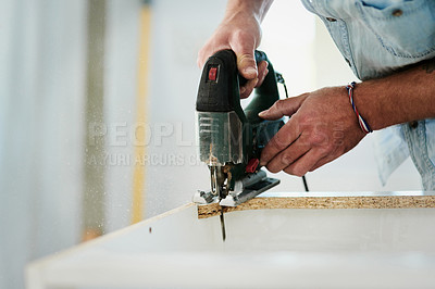 Buy stock photo Cropped shot of a man using a power tool to cut a piece of wood at home