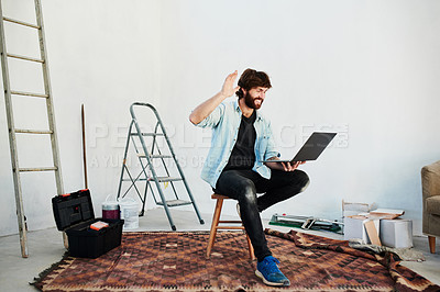 Buy stock photo Shot of a young man using laptop to make a video call while renovating a house