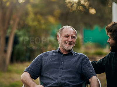 Buy stock photo Cropped shot of a handsome young man sitting outside with his elderly father
