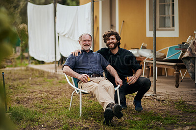 Buy stock photo Full length portrait of a handsome young man sitting outside with his elderly father