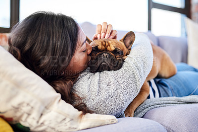 Buy stock photo Shot of a young woman relaxing with her dog at home