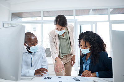 Buy stock photo Shot of a group of businesspeople wearing face masks while going through paperwork together in an office