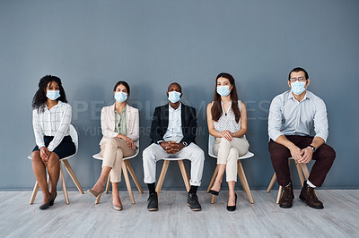 Buy stock photo Portrait of a group of businesspeople wearing face masks while sitting in line against a grey background
