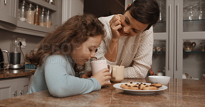 Buy stock photo Shot of a little girl and her mother having hot chocolate and cookies at home