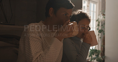 Buy stock photo Shot of a little girl and her mom enjoying a hot beverage while sitting on the couch at home