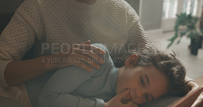 Buy stock photo Cropped shot of a little girl lying on her mother's lap at home