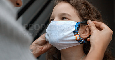 Buy stock photo Cropped shot of a woman putting a mask on her young daughter at home