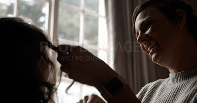 Buy stock photo Cropped shot of a woman braiding her young daughter's hair in the bedroom at home