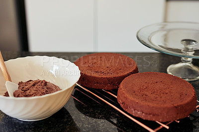 Buy stock photo Shot of two freshly baked chocolate cakes cooling on a rack in the kitchen a home