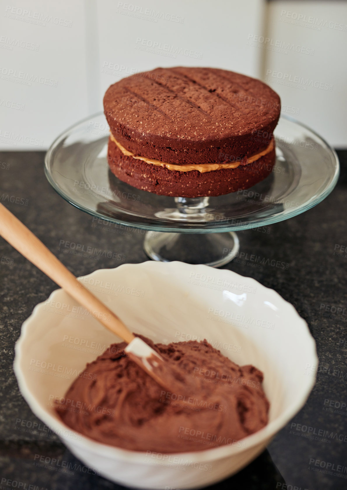 Buy stock photo Shot of a freshly baked chocolate cake on a cake stand in the kitchen a home