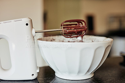 Buy stock photo Shot of chocolate batter dripping off the beaters of a hand mixer on a kitchen counter at home