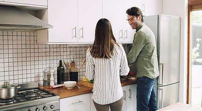 Buy stock photo Shot of a couple cooking together in the kitchen at home