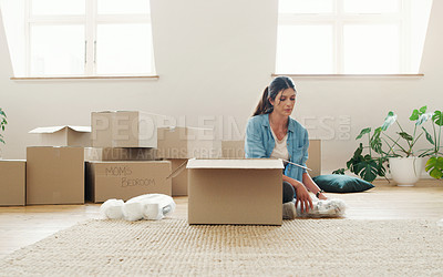 Buy stock photo Cropped shot of a woman unpacking boxes in her new house