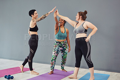 Buy stock photo Shot of a group of young women giving each other a high five after their workout
