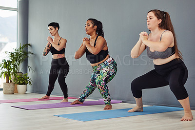 Buy stock photo Shot of a group of young women doing squats in a gym