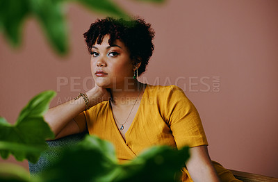 Buy stock photo Portrait of a young woman relaxing with plants around her against a brown background