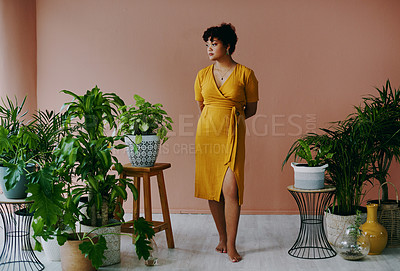 Buy stock photo Shot of a young woman standing with plants around her at home