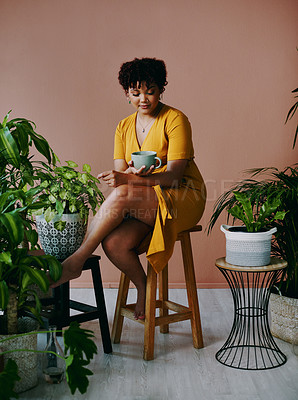 Buy stock photo Shot of a young woman drinking coffee while relaxing with plants around her at home