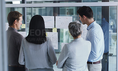 Buy stock photo Rearview shot of a group of businesspeople brainstorming with notes on a glass screen in an office