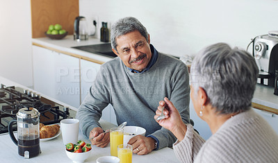 Buy stock photo Shot of a senior couple enjoying a relaxing breakfast at home