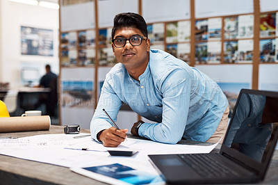 Buy stock photo Shot of a young architect drawing up a building plan in a modern office